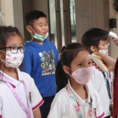 Children in Indonesia having temperature checks